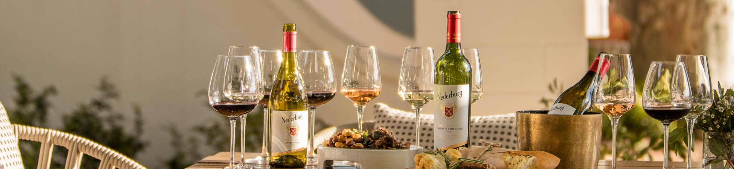 Nederburg Wine poured into glasses, set on a lovely table with matching food.